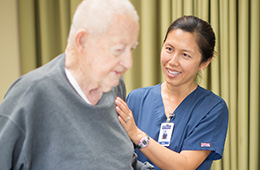 nurse helping older man stand up