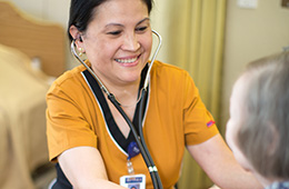 smiling nurse helping a patient with blood pressure