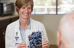 doctor holding up a picture of blueberries and smiling