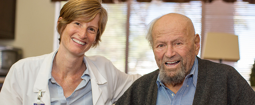 smiling woman doctor and older man standing together
