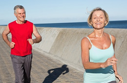 man and woman jogging by water