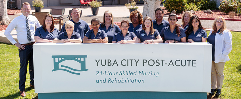 yuba city post acute staff photo with large sign outside on a sunny day