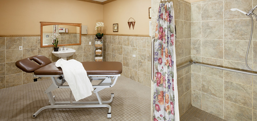 shower area with floral curtains and tiled floors and walls.