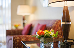 pillows and a couch with lamps and flowers on the side table