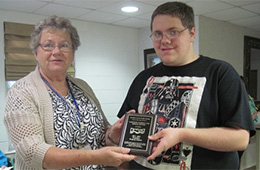 Young man receiving an award from a staff member at Caroline nursing